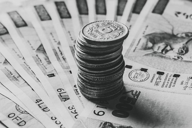 sloupec mincí na vějíři bankovek.jpg