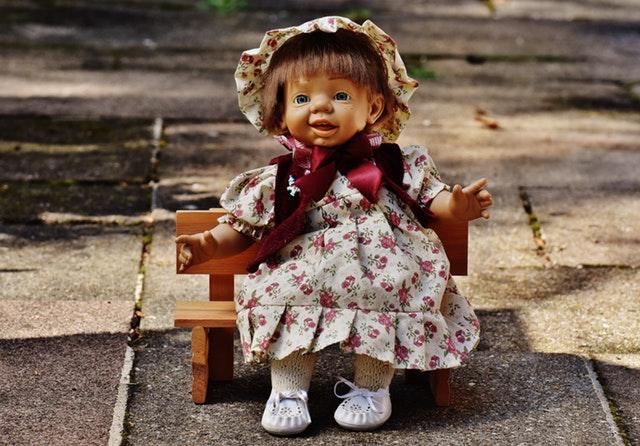 Panenka sedící na malé dřevěné lavičce